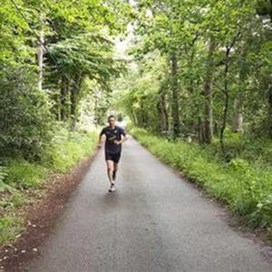 picture of Greg running on a path with woodlands on either side of him.